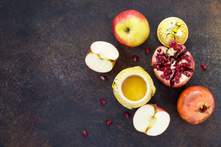 The concept of Rosh hashanah (Jewish New Year). Traditional holiday symbols - honey, apple and pomegranate on a stone or slate background. Flat lay, top view.