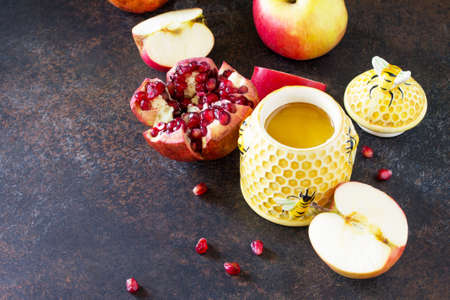 The concept of Rosh hashanah (Jewish New Year). Traditional holiday symbols are shofar, honey, apple and pomegranate on a stone or slate table. Copy space. Lizenzfreie Bilder