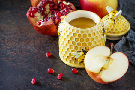 The concept of Rosh hashanah (Jewish New Year). Traditional holiday symbols are shofar, honey, apple and pomegranate on a stone or slate table.