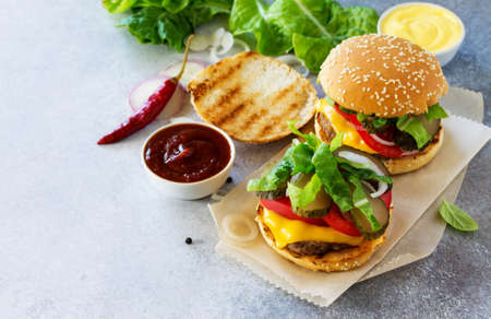 sesame street: A delicious fresh homemade hamburger on a slate or stone table. Cheeseburger with meat cutlet and vegetables. Street food, fast food. Copy space. Stock Photo
