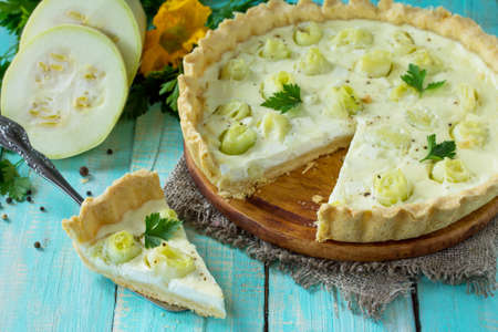 A classic quiche Lorraine pie with feta cheese with zucchini, egg pouring and cheese on a kitchen wooden table.