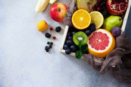 Fresh mixed fruits on a gray stone or slate background. The concept of a healthy diet. Top view with copy space. Stock Photo