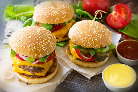sesame street: A double burger with a meat cutlet and vegetables is served with cheese sauce and ketchup. Delicious fresh homemade double cheeseburger on a wooden kitchen table. Street food, fast food.