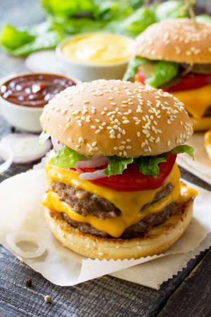 Delicious fresh homemade double cheeseburger on a wooden kitchen table. Double burger with meat cutlet and vegetables. Street food, fast food.