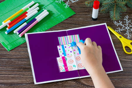 A child glues together a greeting card with Christmas presents. Made by own hands. Childrens art project, craft for children. Craft for kids. Stock Photo