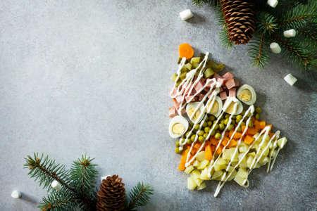 サラダオリビエから作られたクリスマスツリーは、灰色のスレート、石や金属の背景に。美しいクリスマスと新年の背景テキスト用の空白スペース