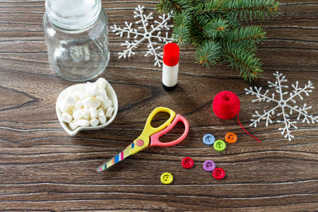 Details of the Christmas gift snowman sweets - marshmallow, jar, thread, scissors, glue, buttons on a wooden table. Childrens art project for children. Craft for kids.