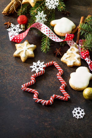 Christmas baking. Christmas gingerbread cookies and star decorations, spices (cinnamon, cloves and anise) on a brown slate or stone background. Copy space. Stock Photo