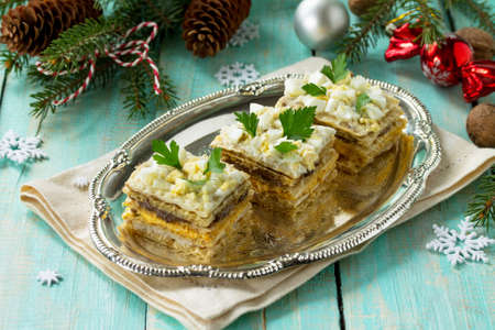 Home holiday snacks Christmas table. Snack cake with a cracker, herring pate, mushroom pate and cheese sauce. Top view with copy space. Stock Photo