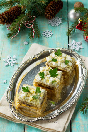 Home holiday snacks Christmas table. Snack cake with a cracker, herring pate, mushroom pate and cheese sauce. Stock Photo