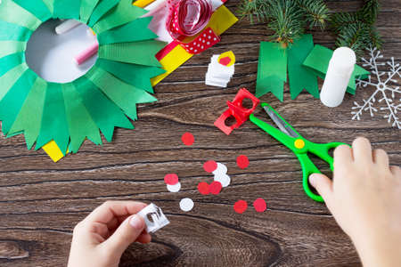 Child carves details Christmas wreath with a candle. Made by own hands. Childrens art project for children. Craft for kids. Stock Photo