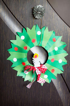 Christmas wreath with a candle. Made by own hands. Childrens art project for children. Craft for kids.