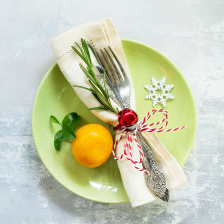 Holiday background. Decor Christmas table on stone or slate background. Green plate, cutlery and decorations. Top view with copy space.