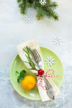 Decor Christmas table on stone background. Green plate, cutlery and decorations. Top view.