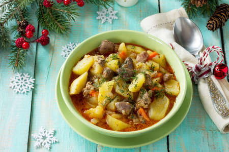 Chicken liver and heart (offal) stewed with potatoes and tomatoes on a festive Christmas table. Stock fotó