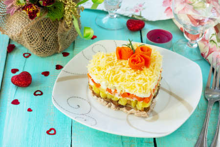 Salad with meat, mushrooms, cheese and vegetables on the festive table on Valentine's Day.  Banque d'images