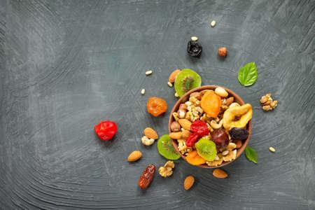 Verschiedene Trockenfrüchte und Nüsse in einer keramischen Schüssel (Walnuss, Acajoubaum, Mandeln, Kiefernnüsse, Haselnüsse) auf einem grauen Stein- oder Schieferhintergrund. Das Konzept eines gesunden Nachtischs. Flachgelegt, Draufsicht.