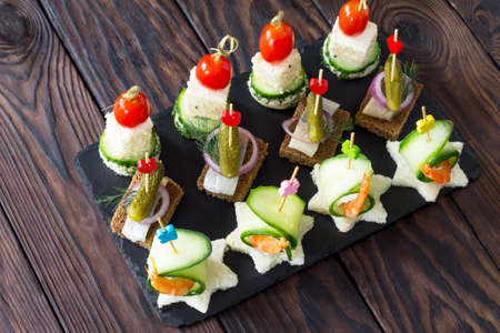 Canape with royal prawns, raw feta and herring on black bread on a slate board. Valentine's Day or wedding.