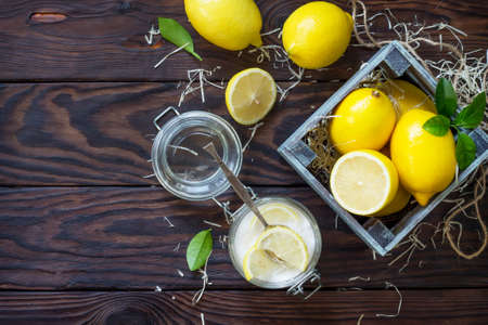 Slices of fresh lemon in sugar and fresh lemons on the kitchen table. The concept of healthy nutrition and diet. Top view flat lay. Stock Photo