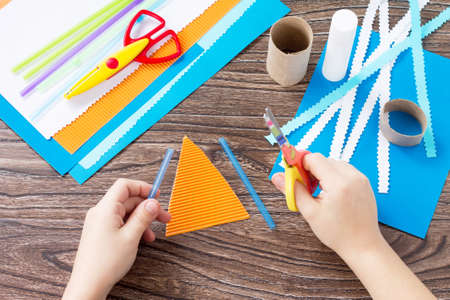 The child cuts out the details of a paper boat, congratulations concept of Father's Day. Glue, scissors and paper on a wooden table. Children's art project craft for kids. Craft for children. Archivio Fotografico