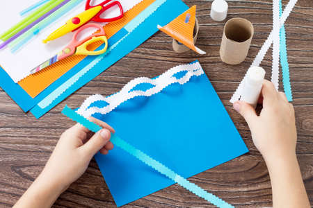 Child sticks paper boat parts, congratulations concept of Fathers Day. Glue, scissors and paper on a wooden table. Childrens art project craft for kids. Craft for children.