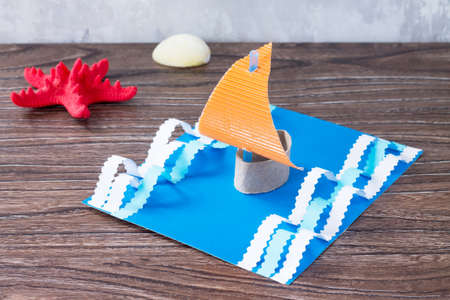 Craft Paper boat, the concept of Father's Day congratulation. Starfish and seashells on a wooden table. Children's art project craft for kids. Craft for children. Stock Photo