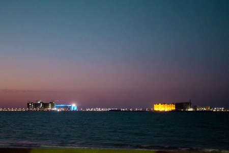 Sunset over the Persian Gulf, framed by a date palma - Ras Al Khaimah. United Arab Emirates. Stock Photo