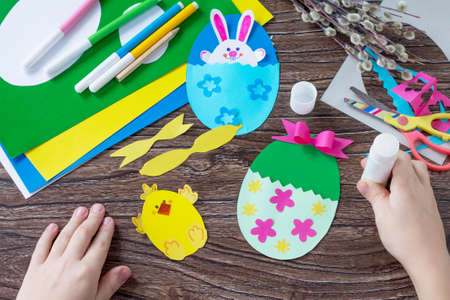 A child glues the details of an Easter egg gift with a chicken and Easter bunny toy. Handmade. Project of children's creativity, handicrafts, crafts for kids.