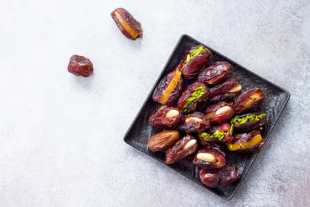 Stuffed dates with nuts and candied fruit filling on a stone or slate background. The concept of a healthy dessert. Flat lay. Top view.