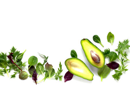 Ripe fresh avocado and mixed salad leaves isolated on white background. Stock Photo