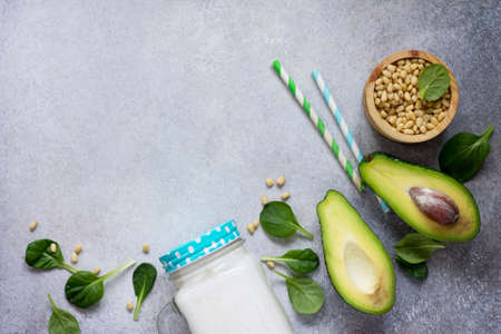 Mug Mason jar with a refreshing milkshake green spinach and pine nuts. Healthy vegetarian food. Top view with space for your text. Stock Photo