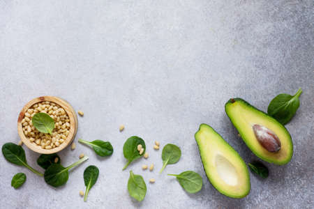 Avocado halves, baby spinach leaves and pine nuts on concrete, stone or slate background. Dietary food, concept of vegetarian food. Top view with copy space.