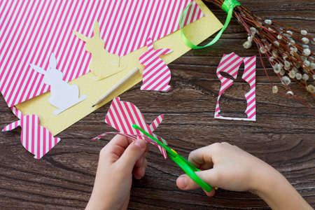 The child draws details festive Easter decor with handmade decoration of colorful rabbits on a wooden background. Project of childrens creativity, handicrafts, crafts for kids.