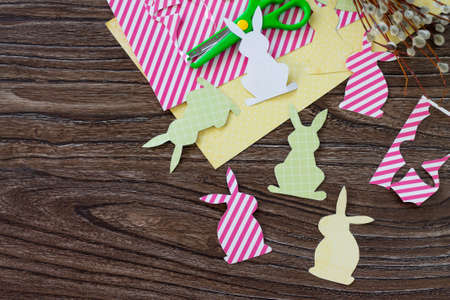 Festive Easter decor with handmade decoration of colorful rabbits on a wooden background. Project of childrens creativity, handicrafts, crafts for kids. Top view with copy space. Standard-Bild