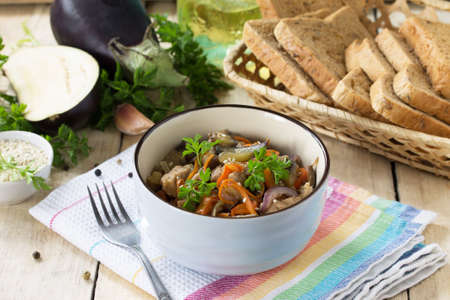 Warm salad with boiled meats and grilled vegetables (eggplant, carrots, paprika) он the kitchen wooden table.