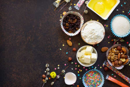 Ingredients for Easter baking - eggs, nuts, flour, yeast, butter, raisins, sugar and willow branches. Seasonal, food background. Flat lay. Top view with copy space. Standard-Bild