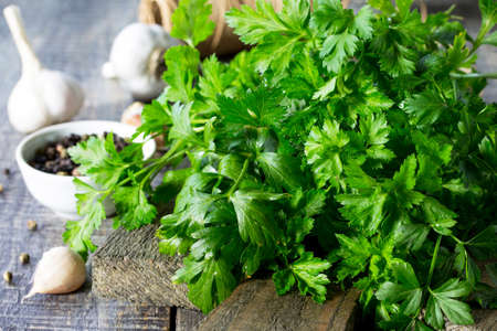 Sprigs of fresh parsley, garlic and various spices on the rustic kitchen table.  Stock Photo