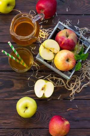 Fresh fruity apple juice and ripe apples on a wooden table. The concept of nutrition for superfoods and health or detoxification. Flat lay. Top view.