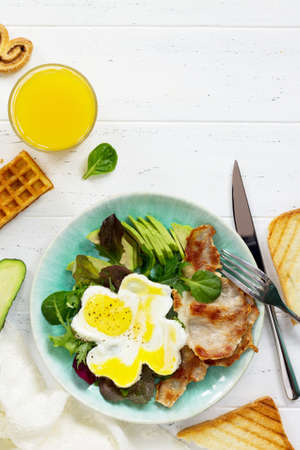 English breakfast - fried egg, fried bacon, spinach, arugula, avocado, toast and orange juice. Top view with copy space.