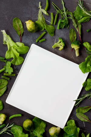 White square plate, various lettuce leaves, rosemary and green vegetables (brussels sprouts, green beans, broccoli) on a dark slate table. Diet, concept of vegetarian food, top view flat lay background. Stock Photo