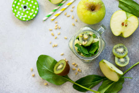 Ingredients for the preparation of green smoothies - apple, kiwi, spinach, pine nuts. Proper nutrition. Copy space, top view flat lay background. Stock Photo