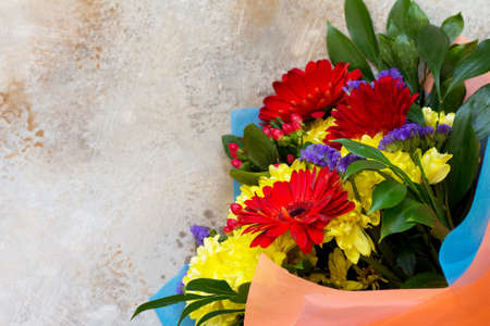 A wedding story or background Mother's Day. Basket bouquet of gerbera and chrysanthemums on a stone background or slate with copy space. Copy space, top view flat lay background. Stock Photo