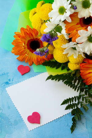 Mothers Day background. Congratulatory sheet of paper withbouquet of gerbera and chrysanthemums on a blue stone background or concrete with copy space.