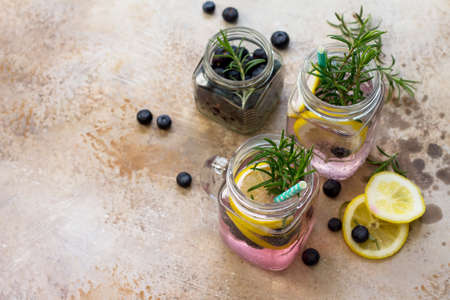 Lemonade or cocktail with blueberries, lemon and rosemary, cold refreshing drink with ice on concrete or stone table. Copy space.