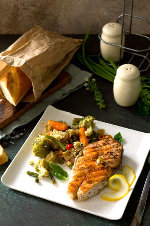 Grilled salmon steak, couscous and vegetables (string beans, brussels sprouts, carrots, sweet peppers, tomatoes) on stone or concrete table. Healthy proper nutrition. Copy space. Stock Photo