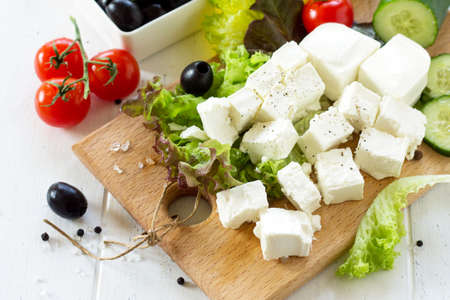 Feta cheese and black olives, cooking qreek salad with fresh vegetables on a white wooden table. Фото со стока