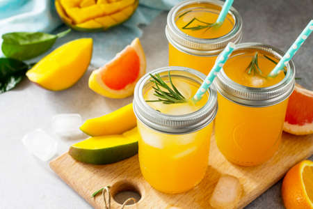 Healthy juicy diet with summer vitamin drinks or a concept of vegetarian food, fresh vitamins, a homemade refreshing fruit drink made of citrus and mango.