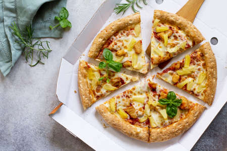 Pizza Hawaiian in a cardboard box on a light stone or concrete background. Space for text. Top view. Pizza delivery. Pizza menu.