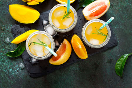 Fresh refreshing summer drinks. Multifruit drinks of citrus and mango with ice, smoothies on a dark stone background. Copy space, top view flat lay background. Stockfoto