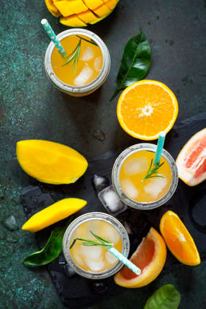 Fresh refreshing summer drinks. Multifruit drinks of citrus and mango with ice, smoothies on a dark stone background. Copy space, top view flat lay background. Imagens